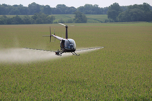 heli-ag helicopter spraying over a farm land
